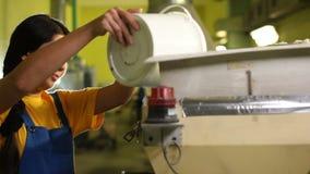 El trabajador de mujer agradable con la trenza oscura larga vierte la mezcla en la máquina almacen de video