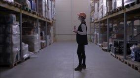El trabajador de mujer en casco utiliza la tableta digital en almacén de la fábrica entre las filas de los estantes del almacenam metrajes