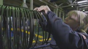 El trabajador de mujer pone los anillos de goma del neumático en soporte especial metrajes