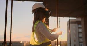 El trabajador de mujer que lleva el chaleco reflexivo tiene experiencia con las auriculares de VR almacen de metraje de vídeo