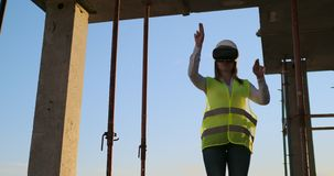 El trabajador de mujer que lleva el chaleco reflexivo tiene experiencia con las auriculares de VR metrajes