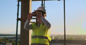 El trabajador de mujer que lleva el chaleco reflexivo tiene experiencia con las auriculares de VR almacen de video