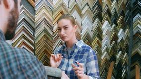 El trabajador de mujer sonriente que charla con el cliente masculino sobre marco detalla cerca de soporte en taller del marco Imágenes de archivo libres de regalías