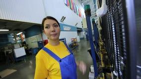 El trabajador de mujer viene trabajar a máquina y presiona los botones almacen de metraje de vídeo