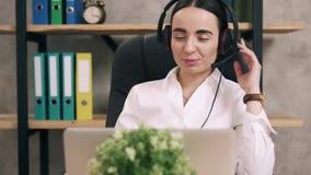 El trabajador de sexo femenino del centro de atención telefónica contesta a llamada de cliente en oficina