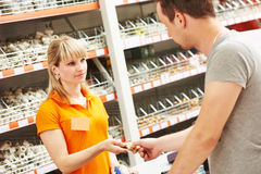 El trabajador de sexo femenino del escritorio de efectivo acepta la tarjeta del pago en la tienda del hardware Foto de archivo libre de regalías