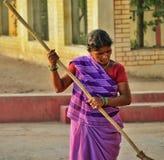 El trabajador de sexo femenino envejecido despeja el piso para despejar los sueños de su niño Imagen de archivo
