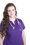 El trabajador de sexo femenino joven de la atención sanitaria con púrpura friega Fotografía de archivo
