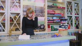 El trabajador de sexo femenino joven de la tienda floral está hablando por el teléfono y el cuaderno de la incorporación almacen de video