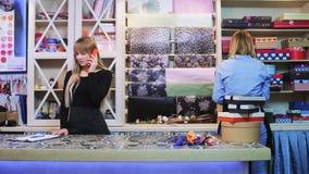 El trabajador de sexo femenino joven de la tienda floral está hablando por el teléfono y está preguntando por algo a su colega almacen de video