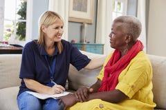 El trabajador de sexo femenino de la ayuda visita a la mujer mayor en casa imagenes de archivo