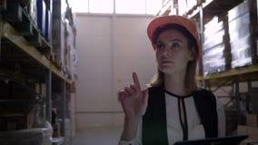 El trabajador de sexo femenino lindo del almacén con la tableta digital a disposición hace inventario y cuenta las cajas metrajes