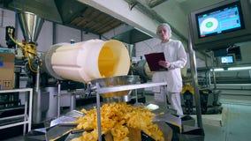 El trabajador de sexo femenino mira una línea de la fábrica el transportar de microprocesadores amarillos almacen de metraje de vídeo