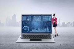 El trabajador de sexo femenino se inclina en el ordenador portátil con la carta Imagen de archivo libre de regalías