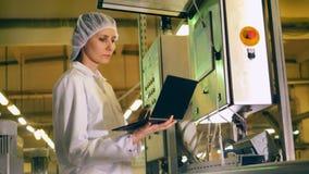 El trabajador de sexo femenino utiliza el ordenador portátil para comprobar la producción alimentaria en una fábrica almacen de metraje de vídeo