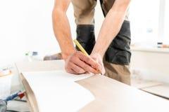 El trabajador de sexo masculino aplica marcas al tablero para cortar con un electrofret vio instalación del nuevo suelo laminado  foto de archivo libre de regalías