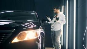 El trabajador de sexo masculino con un buffwheel en su mano está hablando en el teléfono al lado de un coche almacen de metraje de vídeo