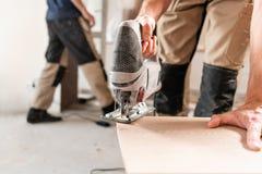 El trabajador de sexo masculino corta al tablero laminado con un electrofret vio instalación del nuevo suelo laminado de madera C imagen de archivo libre de regalías