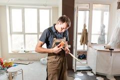 El trabajador de sexo masculino corta al tablero laminado instalación del nuevo suelo laminado de madera concepto de reparación e fotografía de archivo