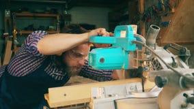 El trabajador de sexo masculino está cortando cuidadosamente la madera con una circular vio Carpintero en taller de la carpinterí almacen de video