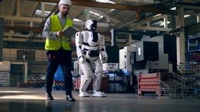 El trabajador de sexo masculino está encendiendo a un cyborg y se está yendo almacen de video