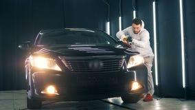 El trabajador de sexo masculino está pulimentando un automóvil negro almacen de video