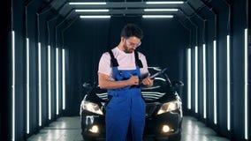 El trabajador de sexo masculino está tomando notas y está sonriendo después de examinar un automóvil almacen de metraje de vídeo
