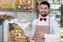 El trabajador de sexo masculino hermoso del café está sirviendo a un cliente Imagen de archivo