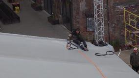 El trabajador de sexo masculino joven se sienta en el borde de la bóveda gris y sostiene la cinta anaranjada a disposición almacen de metraje de vídeo