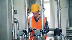 El trabajador de sexo masculino de la destilería está comprobando la presión en tubos almacen de metraje de vídeo