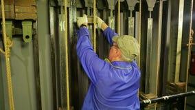 El trabajador de sexo masculino de la escena pone la carga en el mecanismo de elevación de la cortina del teatro almacen de metraje de vídeo