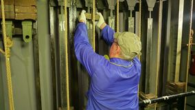 El trabajador de sexo masculino de la escena quita la carga del mecanismo de elevación de una cortina del teatro almacen de video
