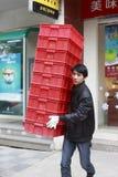 El trabajador de sexo masculino lleva los envases rojos imagen de archivo