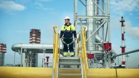 El trabajador de sexo masculino que lleva el casco protector y el subir uniforme hasta las escaleras controlan seguridad en el tr metrajes