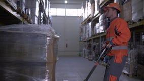 El trabajador de Warehouse saca el camión pesado y tira de él entre las filas de estantes almacen de video
