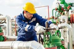 El trabajador del aceite está dando vuelta a la válvula en el oleoducto fotos de archivo