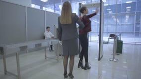 El trabajador del aeropuerto explora un cuerpo del ` s de la mujer con el escáner de la mano en el aeropuerto almacen de video