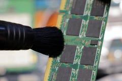 El trabajador del centro de servicio limpia la memoria de acceso del polvo al azar o el tablero electrónico RAM fotos de archivo