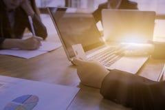 El trabajador del co de las señoras que usa el ordenador portátil y el control cardan a disposición en área de trabajo foto de archivo libre de regalías