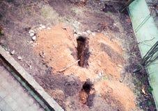 El trabajador del constructor de la gente cava un hoyo para dos hoyos en la yarda de una casa privada fotografía de archivo