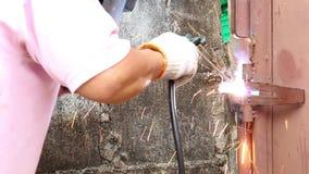 El trabajador del hombre de la reparación está soldando con autógena la puerta de acero en la fábrica Moscas de la chispa de fund almacen de video
