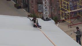 El trabajador del hombre joven se está sentando en el borde de la bóveda gris y está tirando de la cinta anaranjada almacen de video