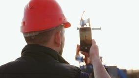 El trabajador del ingeniero en una plataforma petrolera toma la foto con smartphone Industria de petróleo usando la comunicación  almacen de metraje de vídeo