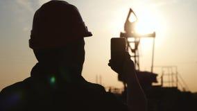 El trabajador del ingeniero en una plataforma petrolera toma la foto con smartphone Industria de petróleo usando la comunicación  almacen de video