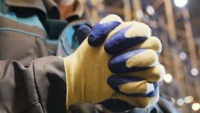 El trabajador del primer de la cámara lenta en guantes aplaude sus manos almacen de metraje de vídeo