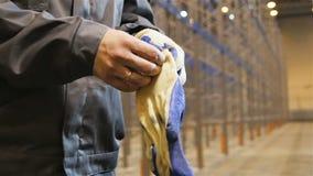 El trabajador del primer de la cámara lenta en uniforme pone guantes almacen de video