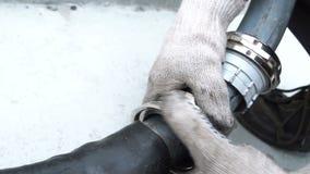 El trabajador del primer en guantes da vuelta a la palanca para conectar el tubo de goma metrajes