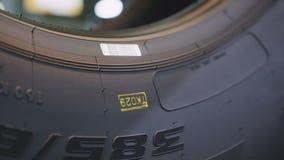 El trabajador del primer hace la marca en lado del neumático del automóvil almacen de video