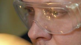 El trabajador del primer hace que la soldadura en fábrica y vidrios refleja las chispas a cámara lenta metrajes
