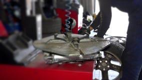 El trabajador del servicio desmonta el neumático del borde de la rueda usando la máquina especial metrajes